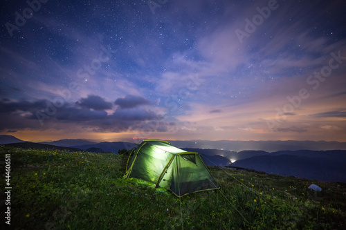 Fotografiet camping in the mountains with a tent at night