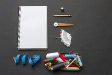Top View Of A White Notebook With Pencil, Scissors, Threads, And Blue Centimeter