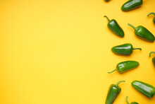 Green Chili Pepper. Group Of Jalapeno Peppers On A Yellow Background, Place For Text, Top View.