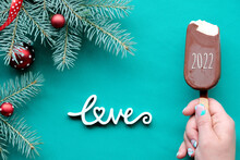 Happy New Year 2022. Hand With Ice Cream. WInter Ackground On Turquoise, Green Textile With Wooden Text Love. Top View On Fir Twigs Decorated With Red Glass Balls, Trinkets.