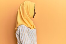 Beautiful African Young Woman Wearing Traditional Islamic Hijab Scarf Looking To Side, Relax Profile Pose With Natural Face With Confident Smile.