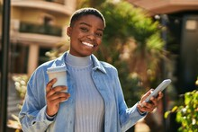 Young African American Woman Using Smartphone And Drinking Coffee At The City