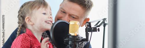 Murais de parede Man and girl are recording their voice on microphone