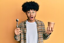 Young African American Man With Afro Hair Holding Ice Cream And Ice Cream Scoop Afraid And Shocked With Surprise And Amazed Expression, Fear And Excited Face.