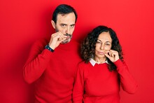 Middle Age Couple Of Hispanic Woman And Man Hugging And Standing Together Mouth And Lips Shut As Zip With Fingers. Secret And Silent, Taboo Talking