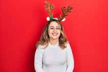 Middle Age Caucasian Woman Wearing Cute Christmas Reindeer Horns With A Happy And Cool Smile On Face. Lucky Person.