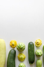 Green Vegetables Zucchini Tomatoes And Squash On A White Table
