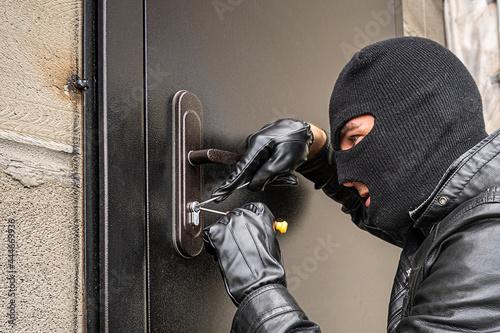Obraz na płótnie man in a black balaclava mask opens a locked door with a lock pick