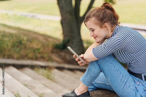 Happy young woman relaxing outdoors with her mobile Tapéta, Fotótapéta