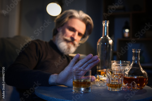 Obraz na plátne Senior man refusing to drink whiskey late in evening at home