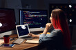 Leinwandbild Motiv Female programmer working with laptop in office at night