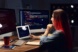 Female programmer working with laptop in office at night