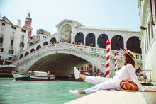 Woman Sitting Near Rialto Bridge In Venice Italy Looking At Grand Canal With Gondolas