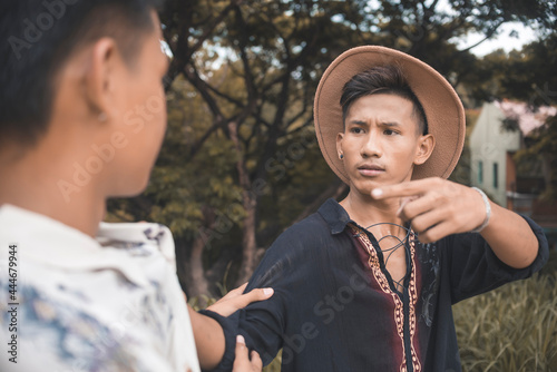 A irate and hotblooded man threatens another guy and points with his hand Fototapeta