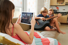 Preteen Girl With Tablet Computer Filming Brother Playing Acoustic Guitar And Singing His Own Song When They Are Spending Time Together At Home