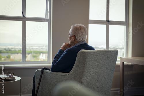Obraz na plátně Lonely senior man looking outside the window
