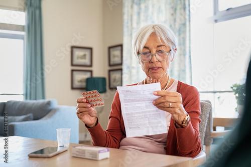 Fotografie, Obraz Senior woman checking medicine leaflet