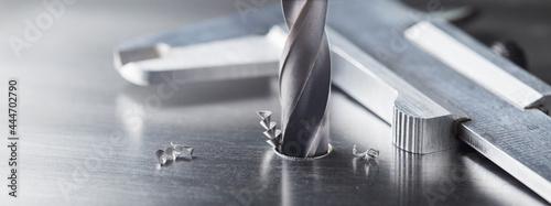 Fényképezés metal drill bit make holes in steel billet on industrial drilling machine