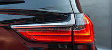 The Red Headlight Of A Modern Black Car. Rear Stop Light Of Large Suv Car. Black Premium City Crossover
