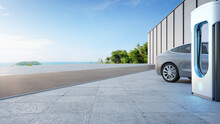 Electric Car On Concrete Floor Near Charging Station In Eco Friendly And Clean Energy Concept. 3d Rendering Of Sea View Plaza With Clear Sky Background.