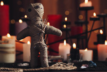 Voodoo Doll With Pins And Dried Flowers On Table In Room, Space For Text. Curse Ceremony