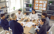 Senior Executive Standing By Table And Talking To Team Of Employees. High Angle Of Group Of Serious Young Male And Female Workers Listening To Director Sitting Around Office Table In Corporate Meeting