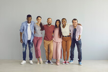 Portrait Of Happy Multiracial Friends In Casual Clothes Who Are Standing Embracing Against The Backdrop Of A Light Wall. Concept Of Friendship Between Different Races And Multinational Young People.