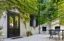 Facade Of A House Facing Its Courtyard With Its Walls Covered By Ivy
