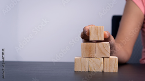 Fotografia, Obraz A woman holding an empty wooden block on the table where she can write any message she wants