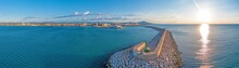 Drone Panorama Of The Spanish Town Of Vinaros With The Large Breakwater At The Entrance To The Port During Sunrise