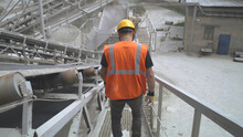 Unrecognizable Male Engineer Walking And Checking Conveyor Belt With Stone