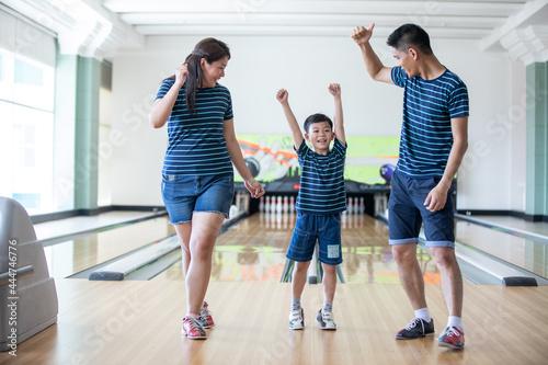 Photo Family having fun at bowling club after skittles bowling ball