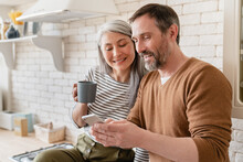 Mature Family Middle-aged Wife And Husband Couple Using Smart Phone Watching Videos, Social Media, Reading News On Cellphone At Home In The Kitchen Together.