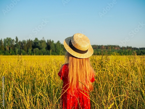 Murais de parede Little happy girl in straw hat and beautiful summer dress walking in field looks at the sunset