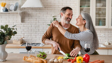 Cheerful Mature Husband Man Cutting Vegetables Cooking Food Meal In The Kitchen While His Wife Woman Embracing Hugging Him Helping Prepare Salad Together At Home