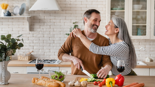 Tela Cheerful mature husband man cutting vegetables cooking food meal in the kitchen