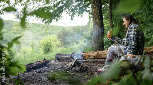 Canvas Print An attractive girl with a cup in her hand warms up near a fire in the forest