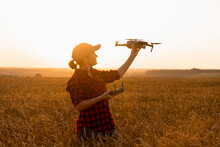 Woman Farmer With Drone On A Wheat Field. Smart Farming And Precision Agriculture