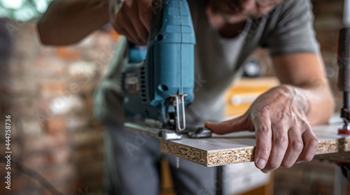 Fotografiet Close-up process of cutting wood board with jigsaw.