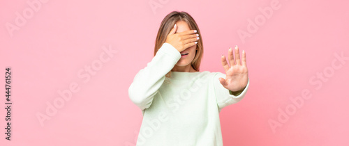 Fotografia, Obraz blonde pretty woman covering face with hand and putting other hand up front to s
