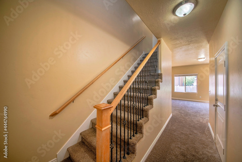 Fotografia Interior of an empty house with stairs and carpeted flooring