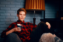 Young Man In Chair Holds Mug Of Hot Chocolate With Marshmallows. Christmas Drink With Sweets And Lollipops. Grey Brick Wall And Floor Lamp On Background. Guy In Plaid Shirt. Festive Atmosphere.