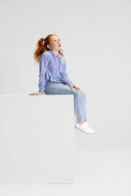One Cute Red-headed Girl In Casual Clothes Sitting On Big Box Isolated On White Studio Background. Happy Childhood Concept. Sunny Child. Looks Happy, Delighted