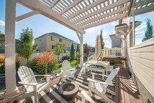 Backyard Of A House With A Pergola Covered Patio Beside The Small Door Deck