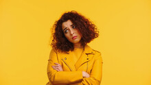 Upset Young Woman In Leather Jacket Standing With Crossed Arms Isolated On Yellow