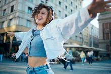Young Happy Girl With Curly Hair Dancing On The Street And Listening Music.