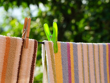 Close-up Of Towels With Clothespins Hanging On A Clothesline Outdoors.
