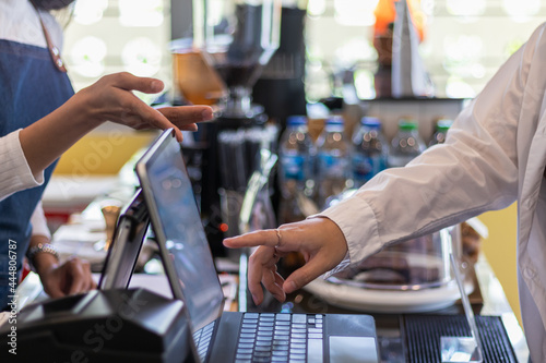 Fotografia, Obraz A young woman who owns a coffee shop and a barista is using a tablet to take orders from a female customer who sits alone inside the shop