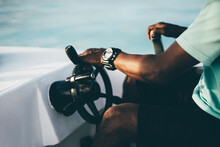 A Close-up View Of A Hand With The Watch Of A Black Adult Guy Turning The Steering Wheel While Driving A Motorboat On A Sunny Evening, Selective Focus, Shallow Depth Of Field