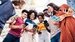 Diverse teenage students using digital smart mobile phones on college campus - Group of friends watching cellphones sharing content on social media platform - Youth, friendship and technology concept